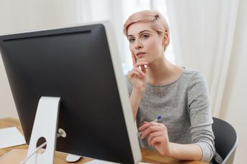 Thoughtful businesswoman working on a desktop