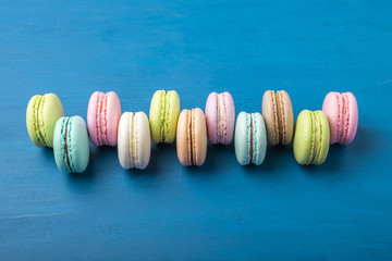 Cake macaron or macaroon on blue background from above, colorful almond cookies, pastel colors, vintage card, top view. Copy space 1