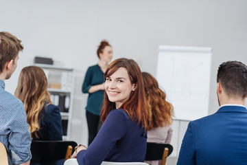 Smiling woman in classroom during seminar