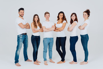 Group of barefoot friends in jeans and white tops