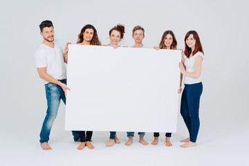 Group of casual barefoot friends with a blank sign