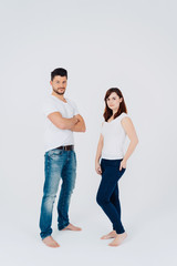 Attractive serious barefoot couple in jeans