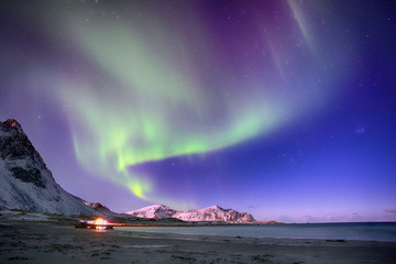 Polar lights in the sky above the mountains on the northern beach in Norway.