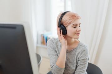 Pretty young woman enjoying music