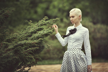 Blonde in a retro style skirt and blouse next to a tree. The girl goes to the garden in a vintage dress.