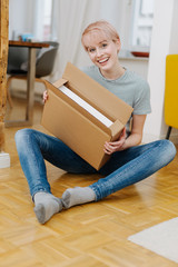 Happy attractive young woman holding a box