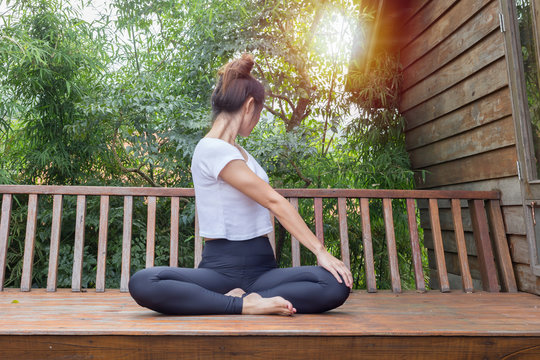 Healthy women relax and practice yoga seated twist pose on wooden terrace with warm light effect in the morning
