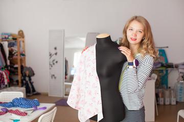 Portrait of female dressmaker adjusting clothes. Small business.