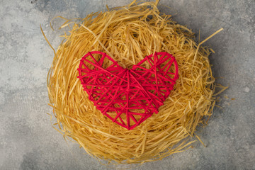Red heart in a bird's nest. The theme of love, family and the day of the holy valentine. View from above. Copy space 1
