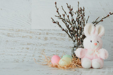 Easter background with colored eggs, sprigs of willow and pink plush Bunny on a light wood texture