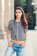 beautiful young girl standing in blue jeans and shirt in the spring on the streets of the city , stylish fashion girl hipster, portrait of a young woman