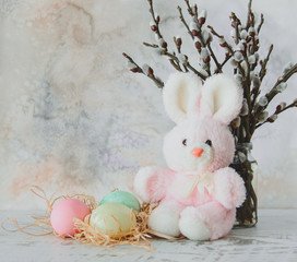 Easter background with colored eggs, sprigs of willow and pink plush Bunny on a light wood texture and watercolor background