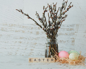 The word Easter from light wooden plates, willow twigs with seals at the Bank and dyed eggs in a nest on a light wooden background