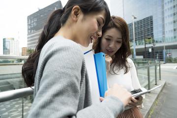 女性達がスマートフォンを操作している