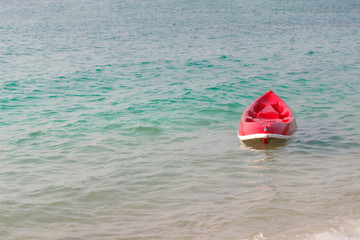 Small red boat on the beach.