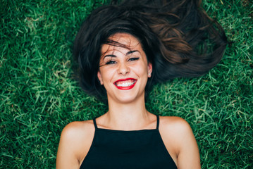 Cheerful brunette woman lying in grass