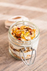 Homemade muesli or granola with nuts and dried fruits with yogurt and honey for healthy breakfast, selective focus