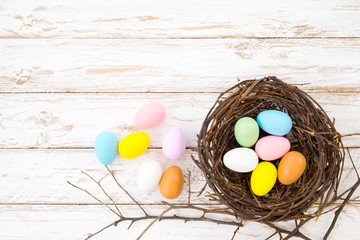 Wall Mural - Colorful Easter eggs in nest on rustic wooden planks background in white paint . Holiday in spring season. vintage color tone style. top view composition.
