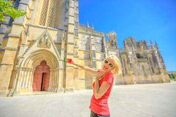 Happy woman takes photo of Batalha Monastery one of the most important Gothic sites in Portugal. Female lifestyle takes pictures by mobile phone with Portugal flag cover.Tourism and travel in Portugal