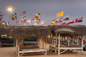 Sunbeds with straw sunshades on sandy beach