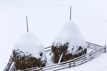 Beautiful rural mountain snowy landscape with haystacks