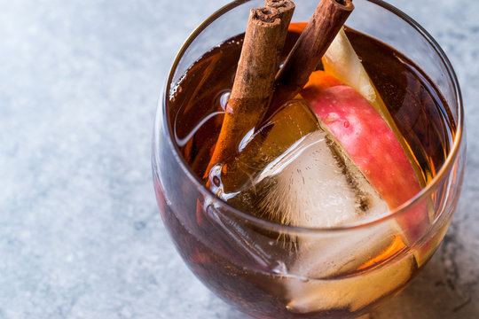 Apple Cider Whiskey Cocktail with Cinnamon Sticks, Ice and Apple Slices.
