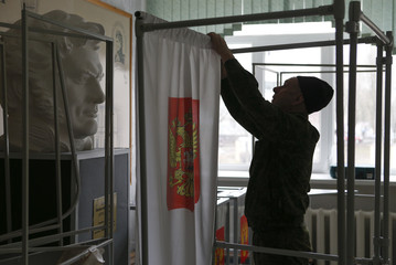 A worker assembles voting booths at a polling station ahead of the upcoming presidential election in Stavropol
