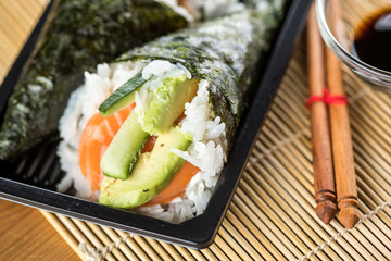 Zwei Lachs Avocado Gurken Temaki Sushi in Bento Box mit Stäbchen und Sojasoße