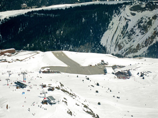 View of the alarmingly short runway of a small Alpine airport in the high altitude ski resort of Courchevel. Surrounding skiing facilities and chair lifts also shown