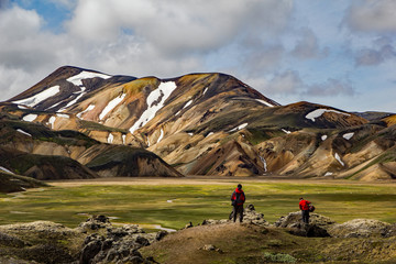 Hiker people near the start of the famous Laugavegur hike, near Landmannalaugar, in Iceland, about to ascend the multi-colored mountains and lava fileds