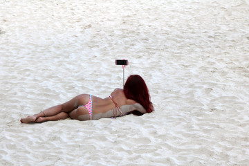 Asian tourists girls wearing bikini enjoy selfies by the smartphone on the sand beach.