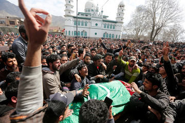 People shout slogans as they gather around the body of Shabir Ahmad, a suspected militant who according to local media was killed in a gunbattle with Indian security forces, during his funeral at Aghanzipora village