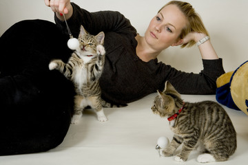 Young woman playing with two small kittens on a white background