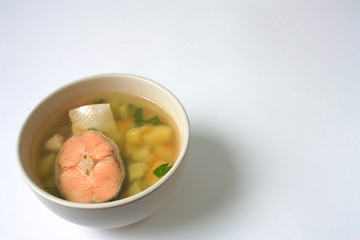 Food- dish salmon fish soup with potatoes and herbs on white surface
