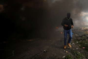 Palestinian demonstrator passes burning tires during clashes with Israeli troops at a protest against Trump's decision on Jerusalem, near Ramallah, in the occupied West Bank