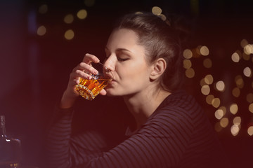 Young woman drinking alcohol in bar