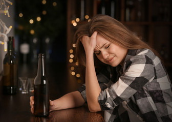 Young sad woman with bottle of drink in bar. Alcoholism problem