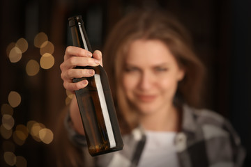 Young woman with bottle of alcohol in bar