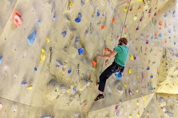 klettern in einer Kletterhalle - Mann klettert an einer Wand mit Sicherung hoch