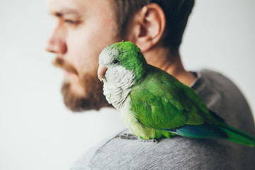Close-up of young beard man with his pet Quaker parrot on shoulder at home
