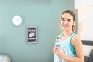 Beautiful young woman with bottle of water after doing fitness exercises at home
