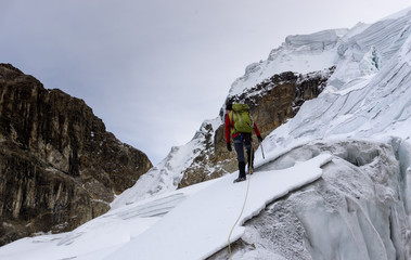 male mountain guide leads the way across a steep glaciere on a high summit of the Cordillera Blanca in the Andes in Peru