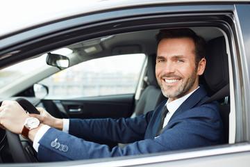 Smiling businessman driving car and looking at camera