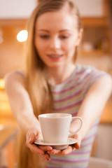 Happy woman holding cup of tea of coffee