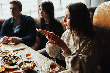 Young girl is taking pictures of food. A young company of people is smoking a hookah and communicating in an oriental restaurant. Lebanon cuisine served in restaurant.  Traditional meze lunch