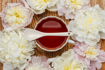 Flat lay over wooden background with peonies, cup of tea and spoon