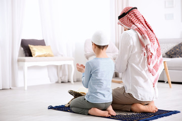 Muslim man praying with son at home