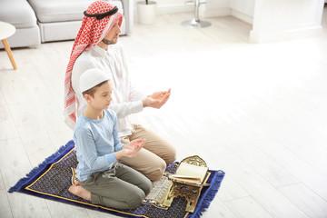 Muslim man praying with son at home
