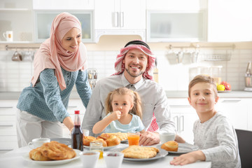 Happy Muslim family having breakfast together at home