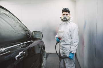 Painter inside paint booth with car